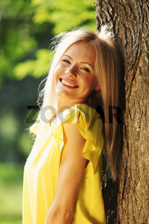 happy woman posing against a background of trees