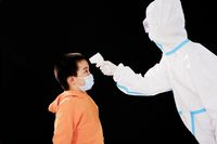 The woman doctor in medical protective clothing took the boy's temperature