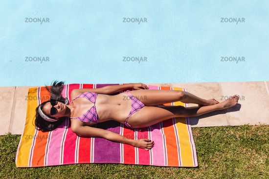 Mixed race woman sunbathing by pool on a sunny day