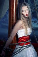 The beautiful girl adhered to a ship mast