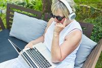 Freelancer Frau sitzt nachdenklich am Laptop im Garten