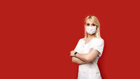 Confident female doctor wearing protective face mask standing on red background. Young woman intern in medical clothes posing.
