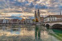 Zurich Switzerland, sunrise city skyline at Grossmunster Church and Munster Bridge with with autumn foliage season