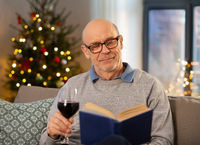 senior man drinks wine and reads book on christmas