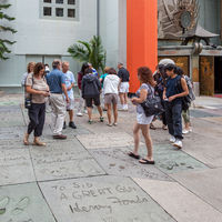 HOLLYWOOD, CALIFORNIA, USA - JULY 29 : People looking at the handprints, footprints and signatures of the stars in Hollywood on July 29, 2011. Unidentified people