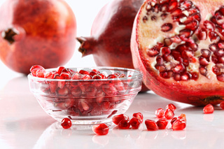 Ripe pomegranates and bowl of seeds on white