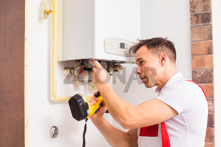 The plumber repairs a boiler at the kitchen