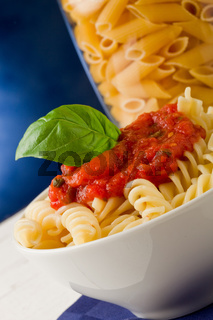 Pasta with tomato sauce and basil on blue background