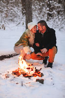 Happy family couple in love basking by camp fire outside in winter snowy forest