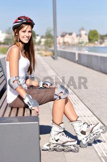 Junge Frau sitzt nach dem Sport auf einer Bank