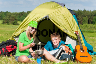 Young camping couple cooking meal outside tent