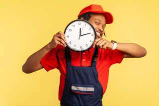 Handyman holding big wall clock in hands, assures the work ill be done on time, service industry.