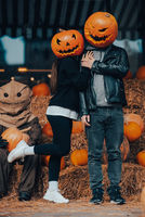 A guy and a girl with a pumpkin heads posing at the scarecrow