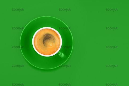 One full espresso coffee cup with saucer on green