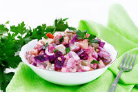 Salad with herring and beetroot in bowl on wooden board