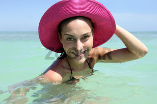 Woman swimming in the sea wearing pink hat