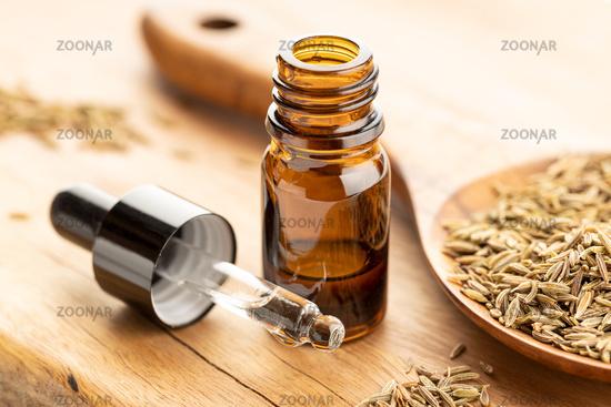 Cumin essential oil bottle on wooden table. Cuminum cyminum