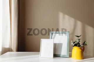 Yellow ceramic jug or vase with eucalyptus branches, empty white photo frames