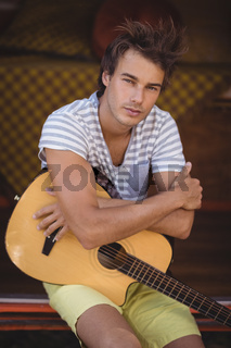 Portrait of handsome man with guitar sitting in van
