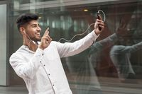 Young man smiling happy doing video call using smartphone at city.