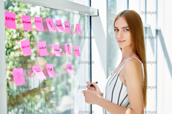 Attractive confident business woman using sticky notes to write and share ideas in creative office