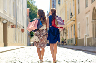 women with shopping bags walking in city