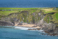 Tourist swimming in the see and relaxing on small hidden Coumeenoole Beach in Dingle