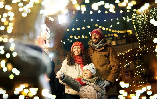 happy family at christmas market in city