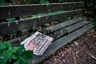 Eine zurückgelassene Bildzeitung liegt auf einer maroden Bank im Leipziger Auwald.