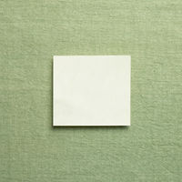 Blank memo pad, empty paper on green fabric background. top view, copy space