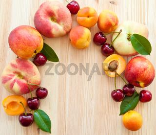 Hintergrund mit frischem Steinobst, Pfirsiche, Kirschen und Aprikosen