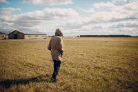 Man walking in grass field in autumn dressed