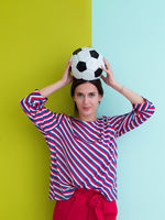 Portrait of young European woman holding soccer ball on her head