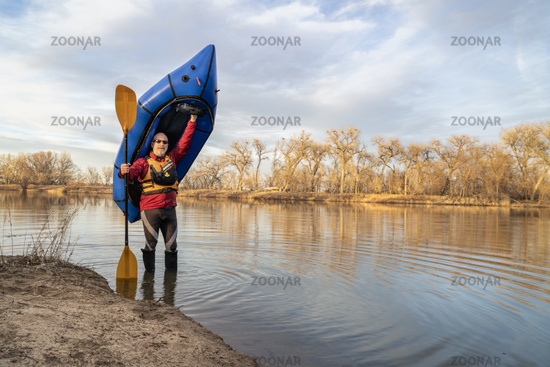 happy senior male  paddler with an inflatable packraft