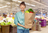 happy asian woman with food in paper shopping bag