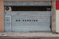 closed shutter on store or shop front saying no parking   -