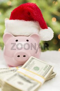 Pink Piggy Bank Wearing Santa Hat Near Stacks of Money on Snowflakes