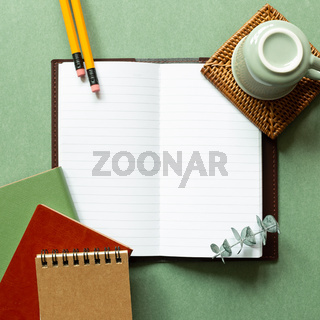 Open notebook, coffee cup, pencil on green background. top view, copy space. workspace, study concept