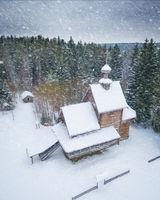 wooden church under the snow. A church near the forest.