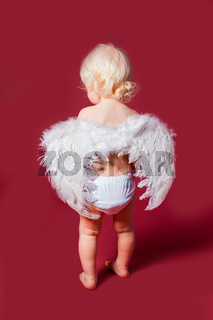 Toddler wearing angel white feather wings and stanc back.