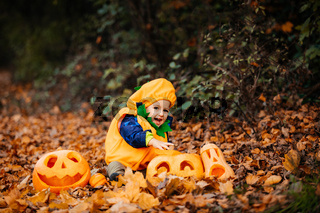 Cute boy in pumpkin costume among carved pumpkins