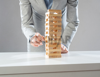 Businesswoman removing wooden block from tower
