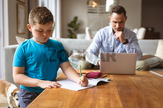 Caucasian father using laptop while son doing his homework at home