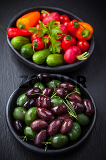 Mixed olives with raw snack vegetable as antipasti