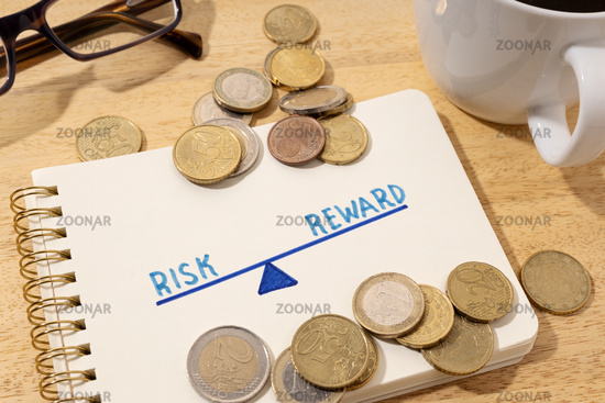 Risk reward concept. Drawing on notepad and coins on desk