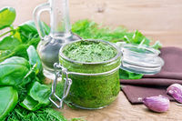 Sauce of spicy greens in jar on old board