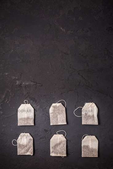 Assorted tea bags on black stone background