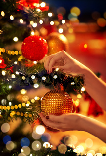 hands decorating christmas tree with ball