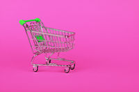 Close up retail shopping cart over pink