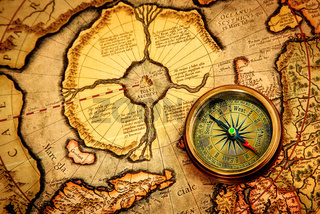 Vintage compass lies on an ancient map of the North Pole.
